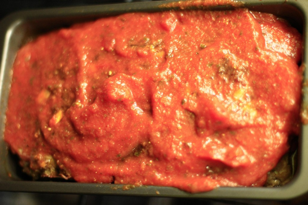 Meatloaf baking with a topping of pasta sauce