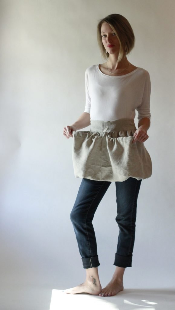 Oatmeal Linen Gathering Apron with its drawstring allowing the apron to be shaped into two large pockets.