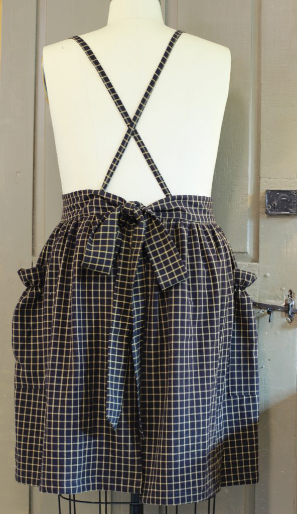 Gathered Bib Apron with its straps crossed and waist ties tied in back.